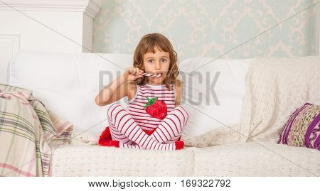 Little cute girl in a striped dress and striped stockings sitting on the couch and eating striped candy