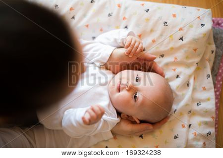 Unrecognizable mother caressing her cute baby son lying on a blanket.