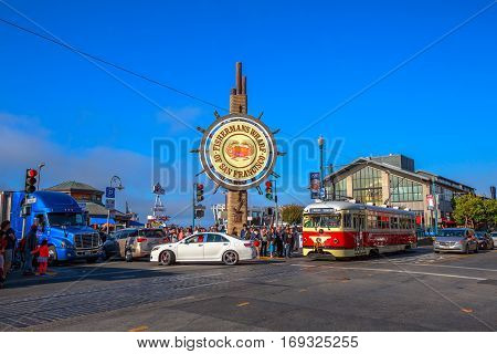 San Francisco, California, United States - August 14, 2016: large sign at entrance to tourist attraction of Fisherman's Wharf. Vintage streetcar from Embarcadero at Jefferson corner Taylor rd.