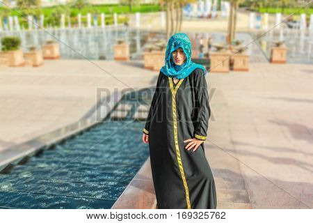 Smiling woman with typical Arab clothes outdoors. Blurred background at Abu Dhabi, United Arab Emirates. Luxury vacations and tourism concept.