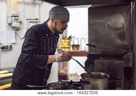 Young male chef in black uniform cooking in restaraunt kitchen