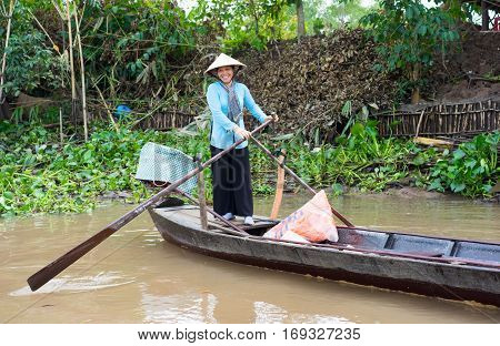 An Giang, Vietnam - Nov 29, 2014: Rural woman rows tourism boat in Tien river, Mekong delta, southern Vietnam. There are more and more tourists come to Mekong delta to enjoy the living in rivers