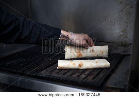 Burrito roll preparing, closeup. Cafe or restaraunt kitchen