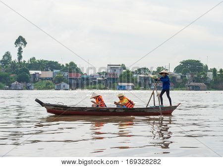 An Giang, Vietnam - Nov 29, 2014: Tourists carried by rowing boat on Tien river, Mekong delta. They enjoying cellphone instead of seeing beautiful scene around
