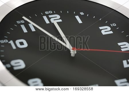 Close up to generic black and silver wall clock showing at the eleventh hour