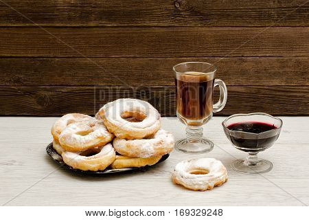 Donuts in powdered sugar a mug of tea and currant jam on a wooden background