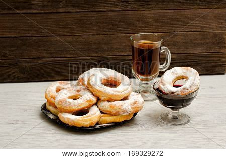 Donuts with icing sugar a mug of tea and currant jam on a wooden background