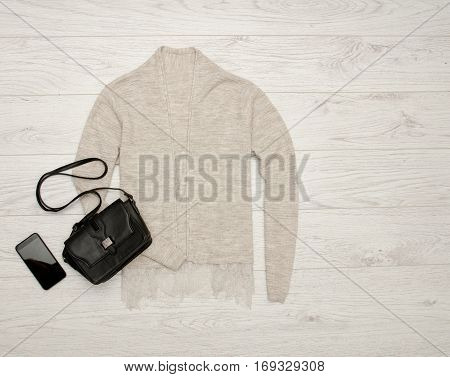 Gray-beige cardigan with lace black handbag phone. Fashion concept. Top view space for text