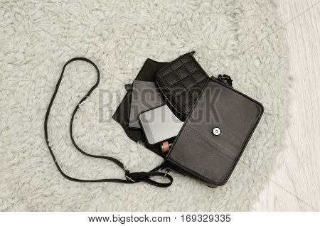 Open black handbag wallet mobile phone and lipstick in it. Grey fur background top view. fashion concept