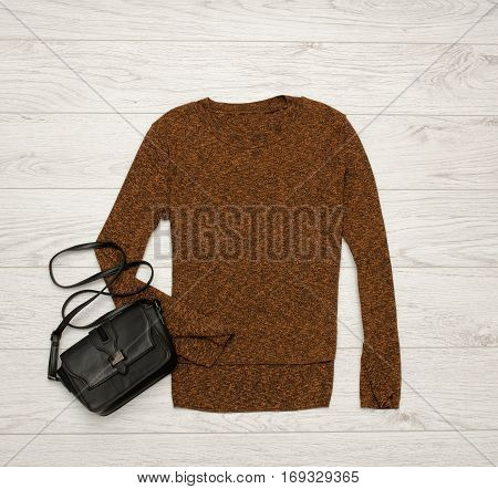 Brown-black sweater and black bag on a wooden background. Fashion concept. top view