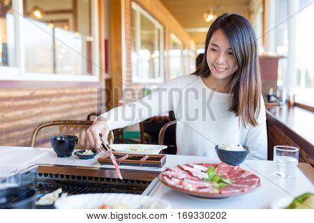 Woman having roasted sliced of beef in japanese yakiniku