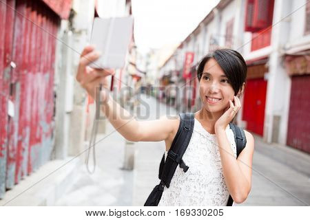 Woman taking photo by digital camera in Macao old town
