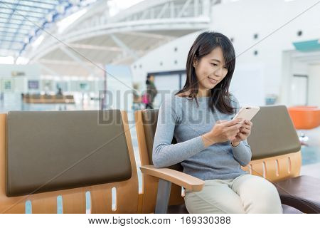 Woman using cellphone and sitting at departure hall