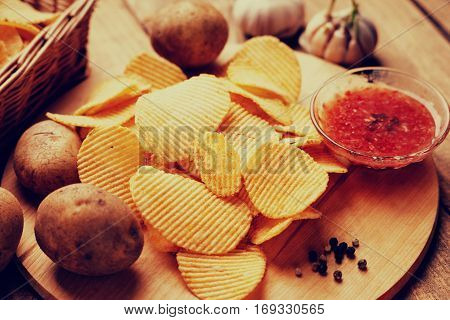 Crispy potato chips, potato and sauce on a wooden cutting board