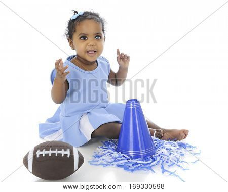 An adorable baby in her cheer leading outfit, happily sitting with her pompoms, megaphone and football.  On a white background.