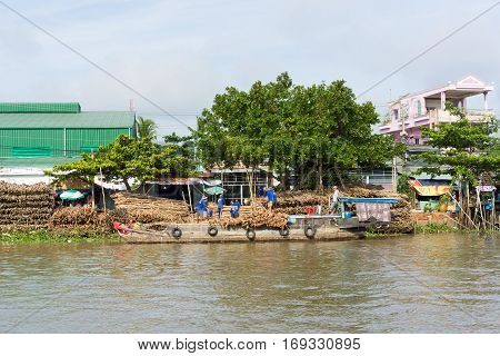 An Giang, Vietnam - Nov 30, 2014: Wide view of river scene, local people carry wood from land to transportation machine boat