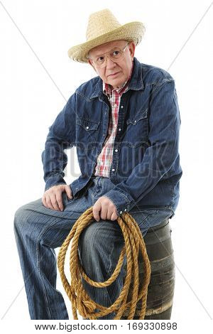 A senior adult cowboy resting on an old barrel with a rope in his hand.  On a white background.