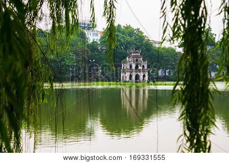 Hanoi Vietnam. Turtle Tower at Hoan Kiem Lake in Hanoi Vietnam. Tree at the foreground cloudy moody weather