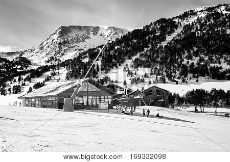 Slopes of Winter Resort El Tarter and Pyrenees Mountains in Andorra la Vella. Restaurant and cafe building unidentified people skiing. Black and white