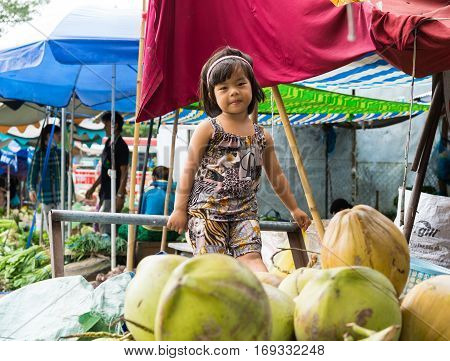 Vinh Long, Vietnam - Nov 30, 2014: Unidentified child plays alone among a lot of fruits at Vinh Long market, Mekong delta. Almost local people at market are poverty