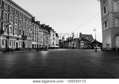 Early morning in Warsaw Poland at the empty Palace square. Illuminated historical buildings. Black and white