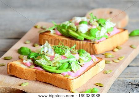 Open avocado sandwiches on wooden background. Homemade sandwiches made with sliced avocado, fresh lettuce, basil and pumpkin seeds. Delicious healthy breakfast recipe