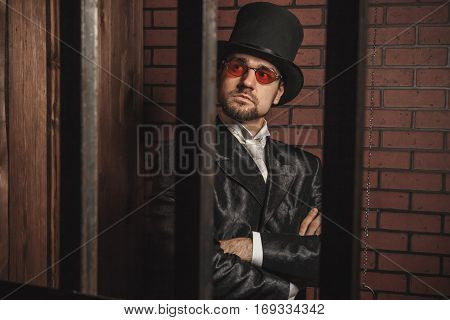 Smart Gentleman In Cylinder Hat And Tie In The Prison Cage.