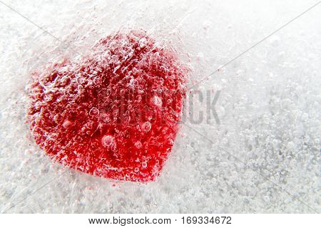 Red heart frozen in ice, macro, selective focus, abstract background
