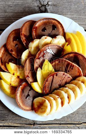 Chocolate pancakes with fruit. Homemade chocolate pancakes with syrup, sliced fresh bananas and apples on a white plate. Top view. Vertical photo