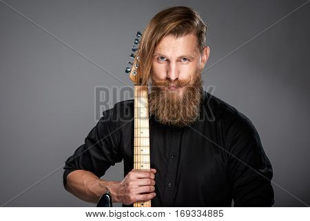 Closeup portrait of hipster man with beard and mustashes wearing black shirt holding guitar, over grey background
