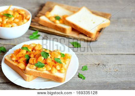 Baked beans with vegetables on white bread and on plate. Baked white beans in a bowl, bread slices, parsley sprigs on wooden background with copy space for text. Healthy diet food