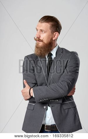 Confident stylish business man with beard and mustashes in suit standing with folded hands looking to the side at blank copy space over grey background