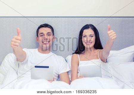 hotel, travel, relationships, technology, intermet and happiness concept - smiling couple in bed with tablet computers showing thumbs up