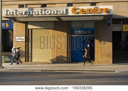 Hanoi, Vietnam - Sep 14, 2014: People walking on sidewalk in front of Citibank ATM on Trang Tien street