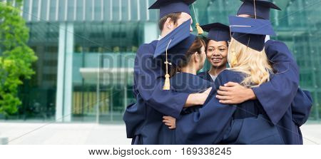 education, graduation and people concept - group of happy international students in mortar boards and bachelor gowns hugging over university building background