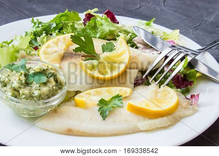 steamed tilapia fish with salad and tartar sauce with appliances on dark background