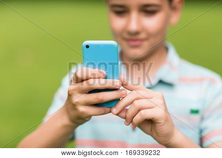 childhood, augmented reality, technology and people concept - boy with smartphone playing game outdoors at summer