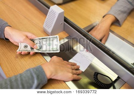 people, withdrawal, saving and finance concept - customer with cash money taking receipt from clerk at bank office or currency exchanger