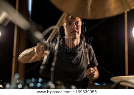 music, people, musical instruments and entertainment concept - male musician in headphones with drumsticks playing drums and cymbals at concert or studio