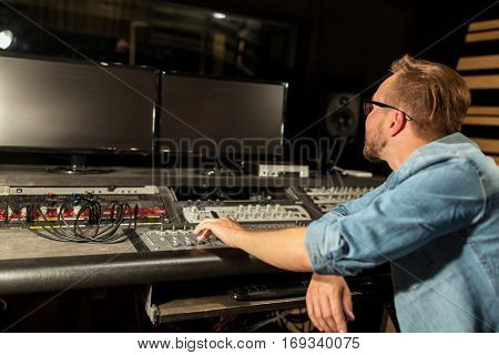music, technology, people and equipment concept - man at mixing console in sound recording studio
