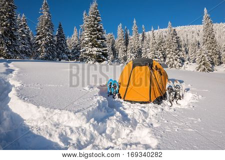 Bright yellow tent and snowshoes at alpine meadow among the snow-covered firs on background colorful sky - magic winter adventure.
