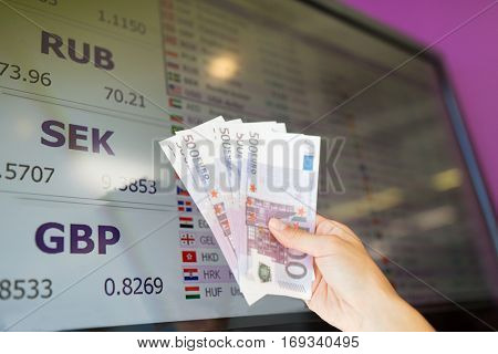 finance, currency conversion and people concept - hand with euro money over exchange rates on digital display screen