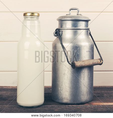 milk bottle and old aluminum can on wooden table