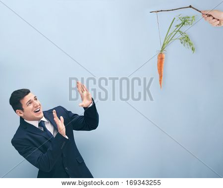 Motivation and goal concept. Young man looking at carrot, color background