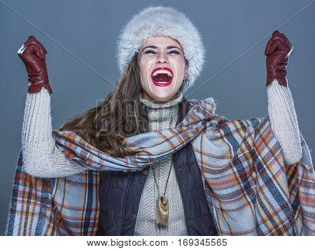 Smiling Modern Woman In Fur Hat Isolated On Cold Blue Rejoicing