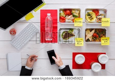 Daily meals delivery. Business lunch at work. Businessman in office with mobile messaging in social networks. Healthy, diet restaurant food in foil boxes, meat and vegetables. Top view, flat lay