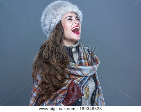 Happy Elegant Woman In Fur Hat Isolated On Cold Blue Rejoicing