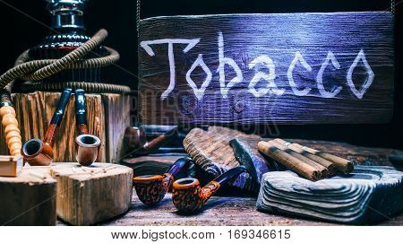 Old-fashioned tobacco showcase. Hookahs, smoking pipes, cigars variety