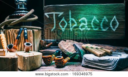Hookah, pipes, cigars, ashtrays and various smokers goods in tobacco shop. Wooden green-lighted sign