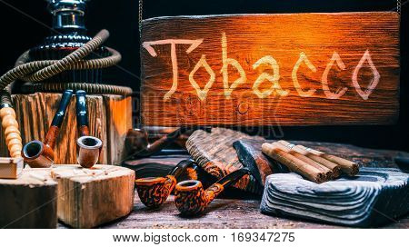 Tobacco store in rustic style. Variety of cigars, smoking pipes, ashtrays, hookah. Natural wood showcase